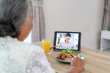 Asian elderly woman virtual happy hour meeting and eating food online together with her daughter in video conference with digital tablet for a online meeting in video call for social distancing..