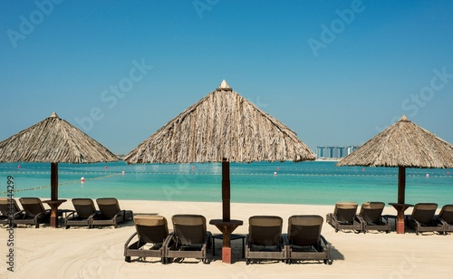 Beach sunbeds and cabanas on the sand, sea view, luxury beach holidays Wallpaper Mural