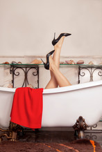 Woman Legs In Black High Heels, Sticking Out From Empty Antique Bathtub On Lion Paws. Luxury Vintage Design Of Bathroom With Marble Walls And Floor, Sea Shells On The Shelves. Indoors, Copy Space.
