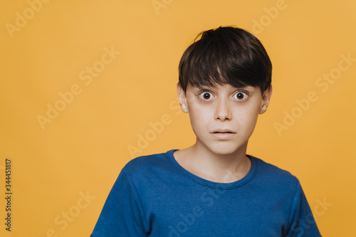 Close up portrait of a pretty caucasian boy in blue t-shirt with wide open eyes, he shocked and afraid, stands over yellow background Wallpaper Mural