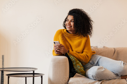 Image of smiling african american woman using cellphone while sitting