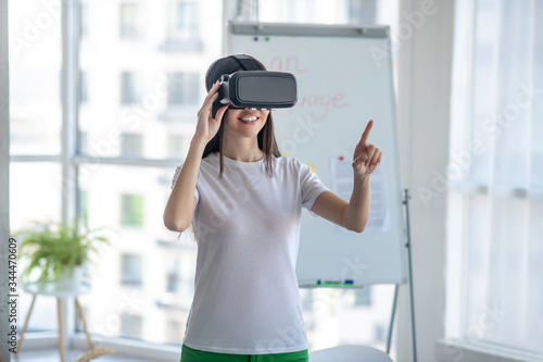 Dark-haired girl standing wearing vr headset and feeling interested Tablou Canvas
