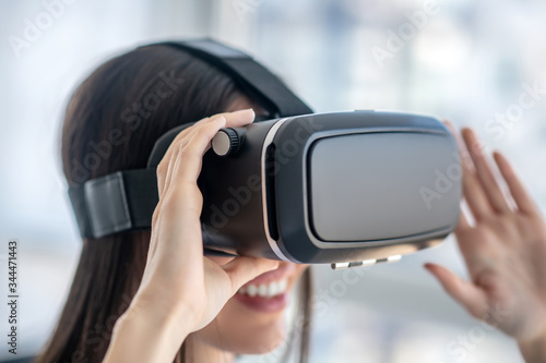 Photo Close up picture of a dark-haired girl attaching vr headset