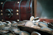 Close-up Of Coins By Wooden Trunk