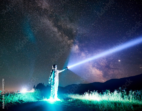 Full length of astronaut illuminating beautiful starry sky with flashlight Canvas Print