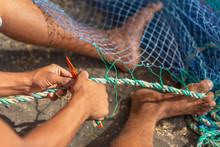 Fisherman Mending Fishing Nets Sitting On The Seashore On The Island Of Santo Antao In Cape Verde On 10/02/2017