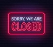 Sorry we are closed neon sign on brick wall background .