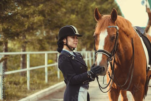 Obraz na plátně horsewoman jockey in uniform standing with black horse outdoors