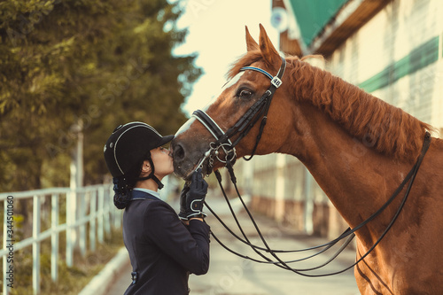 Young teenage girl equestrian kissing her favorite red horse Fototapeta