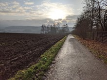 Walking Path Along Plowed Field And Fence In The Afternoon Sun In Rural Germany, With The Sun Glowing Brilliantly Behind Clouds And Mist In The Distance