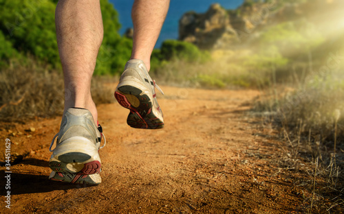 Running outdoors in the mountains by the sea, a dynamic closeup of the male runn Canvas