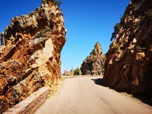 Road Amidst Rocks Against Clear Sky