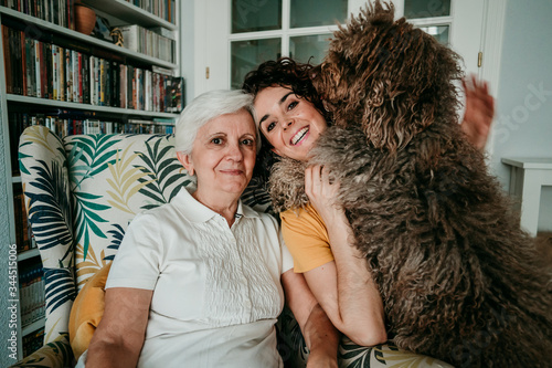 Photo .Adorable portrait of a mother and daughter accompanied by their dog while at ho