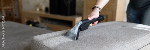 Photographie Male housekeeper hand cleaning sofa with washing suction cleaner