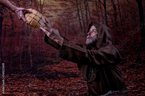 Friar, kneeling in a forest, receiving a loaf of bread Fototapeta