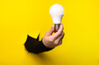Hand holding an incandescent led light bulb from a torn hole in yellow paper