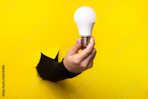 Canvastavla Hand holding an incandescent led light bulb from a torn hole in yellow paper