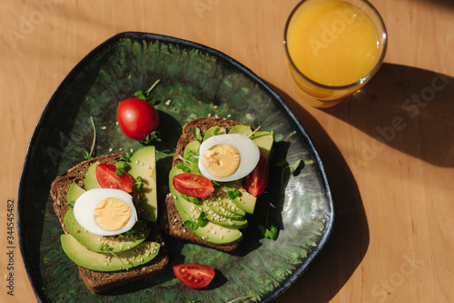 Fototapety, obrazy: Delicious breakfast at home. Sandwich with fresh sliced avocado above rye toasted bread with cherry tomatoes and boiled egg on green plate. Fresh orange juice. Top view