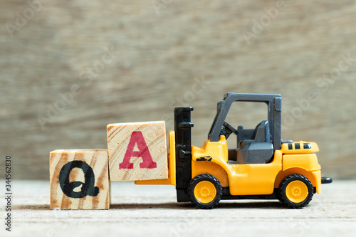 Toy forklift hold letter block A to complete word QA (abbreviation of quality as Canvas Print