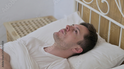 Thoughtful Young Man Awake in Bed Thinking Canvas Print