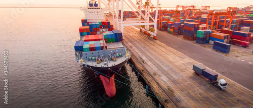Foto crane loanding cargo container to container ship in the international terminal yard port  concept freight shipping by ship at sunrise