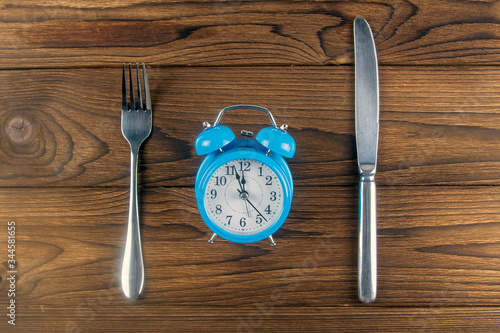 One vintage clock with fork and knife on dark wood table top view Fototapet
