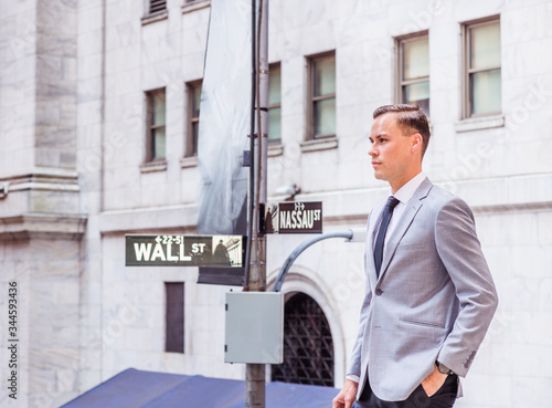 Young European Businessman traveling in New York City, wearing gray blazer, white undershirt, black tie, black pants, standing on street outside office building by Wall Street sign, looking forward Canvas Print