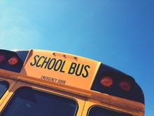 Cropped Image Of School Bus Against Blue Sky