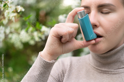 Blond woman with respiratory disease diagnosed with asthma uses an inhaler Fototapeta