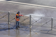 Worker Cleaning Driveway With Gasoline High Pressure Washer Splashing The Dirt, Asphalt Road Fence. High Pressure Cleaning.