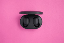 Wireless Headphones In A Mockup Case On A Bright Pink Background With Text Space. Black Earphones In A Case With Charg