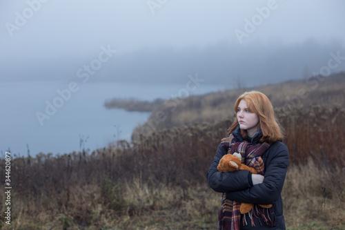 Sad blonde teenager  girl hugging  teddy bear by foggy  lake Wallpaper Mural