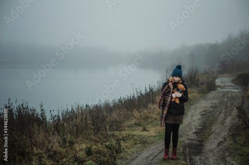 Sad teenager girl hugging  teddy bear by foggy  lake Canvas Print