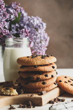 Composition With Chocolate Chip Cookies, Milk And Lilac On White Wooden Table