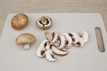 Fresh Organic Brown Mushrooms Champignon And Slice Mushrooms On A White Cutting Board.