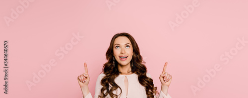 Obraz panoramic shot of cheerful girl pointing with fingers and looking up isolated on pink - fototapety do salonu