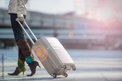 Obraz na plátně Traveler young woman with suitcase walking at th airport terminal