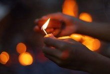 Cropped Image Of Hand Holding Burning Matchstick