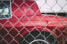 Abandoned Red Car Seen Through Chainlink Fence