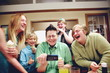 Happy Family Looking In Smart Phone While Enjoying At Restaurant