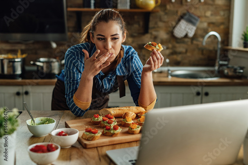Fototapeta Young woman using laptop while eating bruschetta in the kitchen. obraz