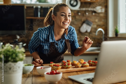 Happy woman preparing food and vlogging over laptop in the kitchen.