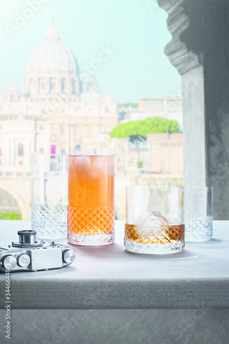 Cold drinks in transparent glasses on the windowsill, view from the window