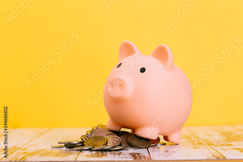 Pink piggy bank on wooden table and yellow background Canvas Print
