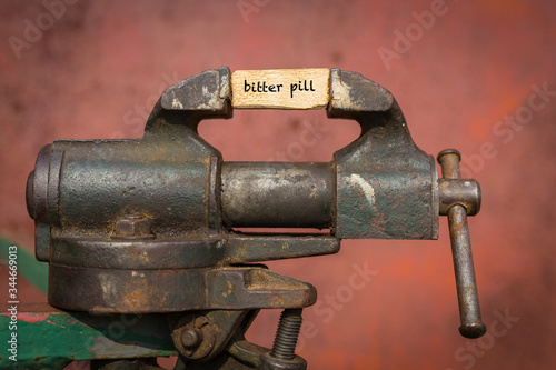 Photo Vice grip tool squeezing a plank with the word bitter pill