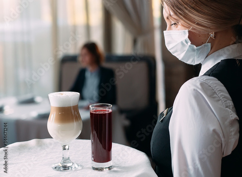 Photo A female Waiter of European appearance in a medical mask serves Latte coffee