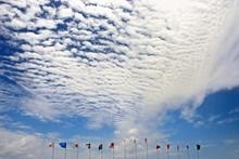 Various Flags Against Cloudy Sky