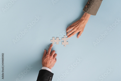 Top view of hands of businesswoman and businessman joining two matching puzzle pieces