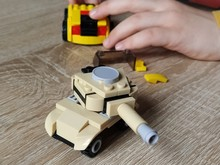 Toy Tank On A Wooden Table. Plastic Toy. Craft From A Childrens Designer. The Beige Color Of The Tank, A Defocused Image Around The Edges. Childs Hand And Fingers