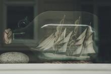 Close-up Of Miniature Ship On Bottle Seen Through Glass